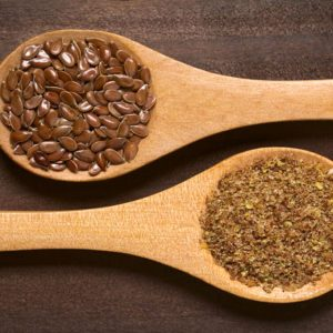 Whole and ground brown flax seeds or linseeds on wooden spoons, photographed on dark wood with natural light