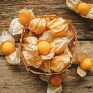 Husk tomato and Ground Cherry in basket on wood table background.