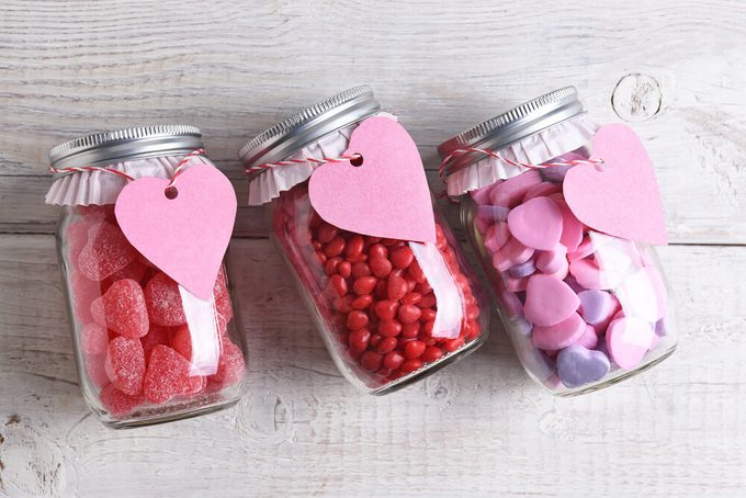 Canning jars laying on their sides filled with candy hearts and for Valentine's Day on a rustic wood table. The jars have blank heart shaped gift tags hanging from the neck