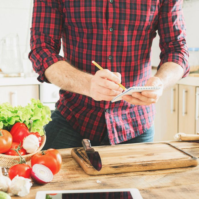 Ingredients for cooking healthy food on a wooden table in a home kitchen. In the background a man writes a recipe to notebook; Shutterstock ID 556856305