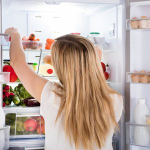 Rear View Of Young Woman Looking At Food In Open Refrigerator