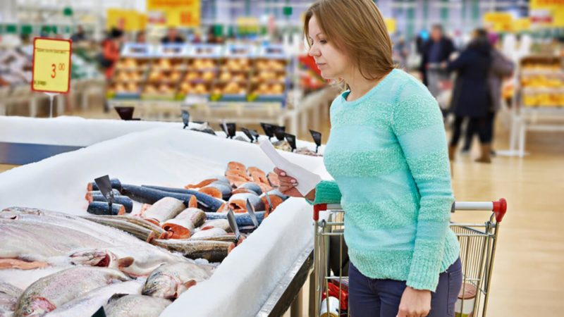 Woman chooses fresh fish in the supermarket