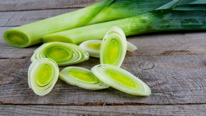 Fresh leeks whole and sliced on a wooden kitchen board
