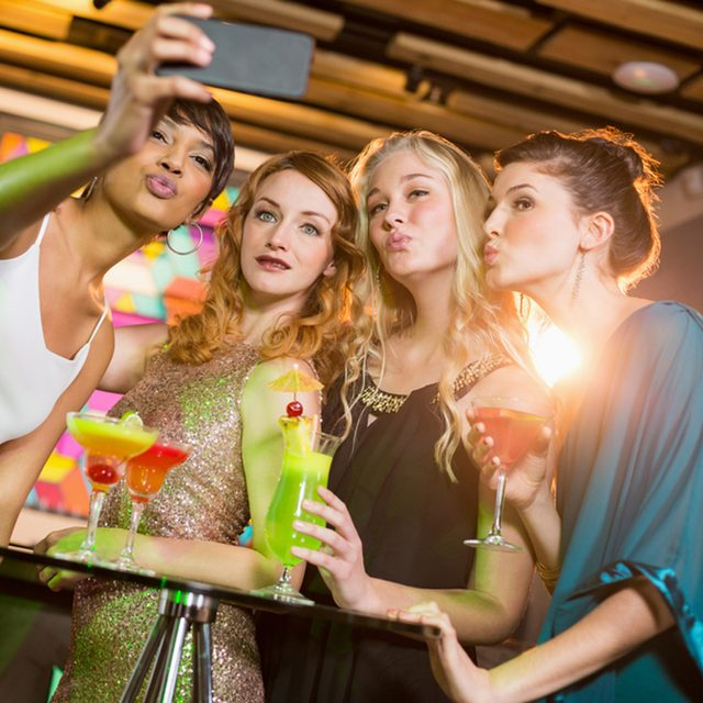 Group of friends taking selfie from mobile phone while having cocktail in bar; Shutterstock ID 585227993