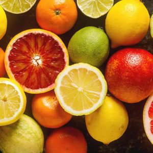 Citrus juice fruit and slices of orange, grapefruit, lemon, lime. Vitamin C. Black background