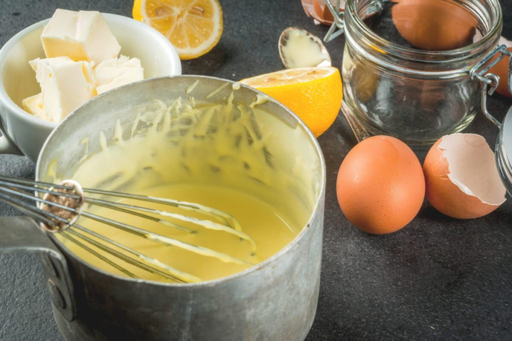 Hollandaise sauce in a metal saucepan, with ingredients for cooking - eggs, butter, lemons.