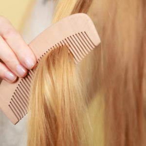 Haircare, choosing best conditioner for tangled hairstyle concept. Blonde woman brushing her hair with comb
