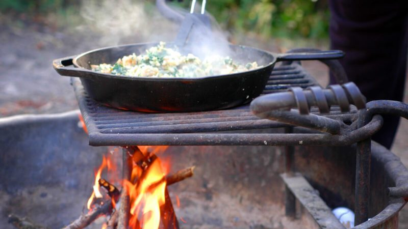 Cooking an egg scramble in a cast iron skillet over a campfire