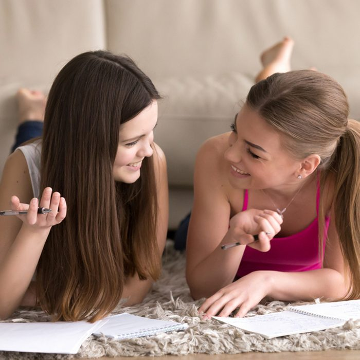 Two cheerful young teenager girls lying on carpet on floor and writing in notepads with pens. Female students studying at home, together preparing for exams, making wish lists, planning their future ; Shutterstock ID 670854397