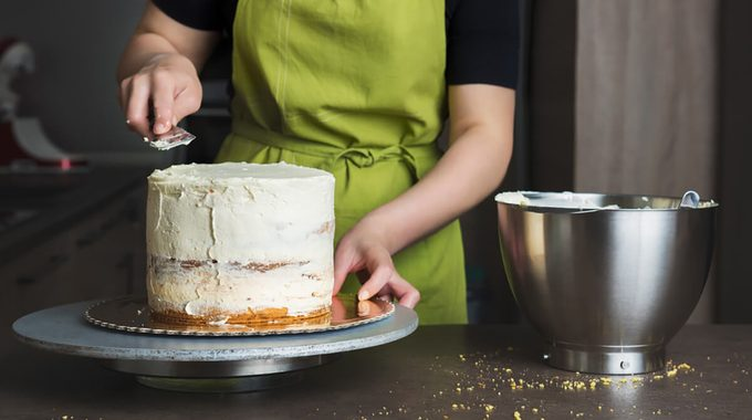 Unrecognisable woman decorating a delicious layered sponge cake with icing cream. DIY, sequence, step by step, part of series.