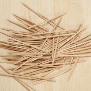 many wooden toothpicks on wooden table background