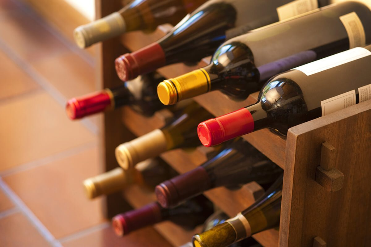 Red and white wine bottles stacked on wooden racks shot with limited depth of field
