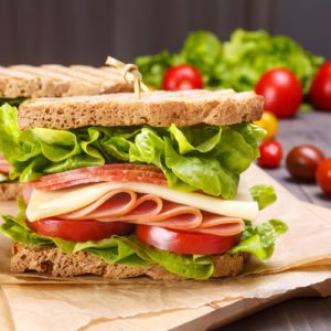 Delicious Ham, Salami, Cheese and Vegetables Sandwiches on Toasted Whole Grain Bread
