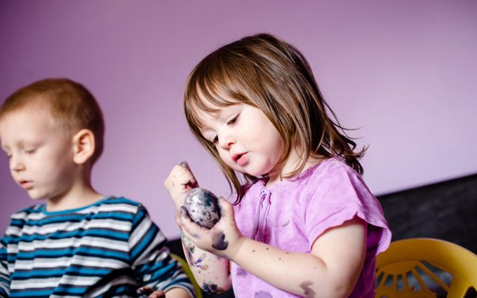 Close up of cute little girl using water colors, painting Easter egg, and her hands also