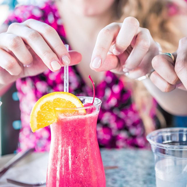 Closeup of two alcoholic summer drinks, strawberry daiquiri and pina colada, in restaurant with people's hands touching, taking straws; Shutterstock ID 783881164; Job (TFH, TOH, RD, BNB, CWM, CM): Taste of Home