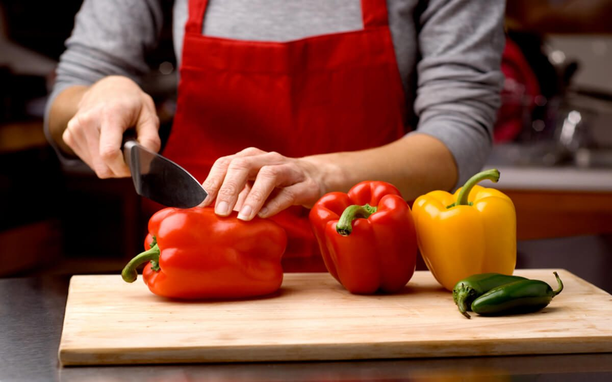 woman slicing fresh bell peppers