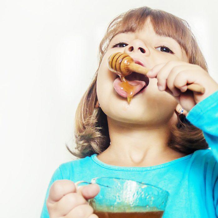 child eating honey