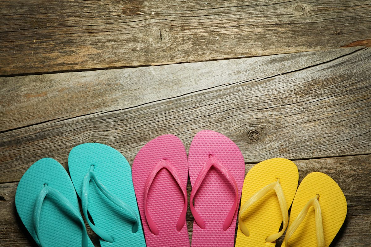 Brightly colored flip-flops on wood. Family vacation;
