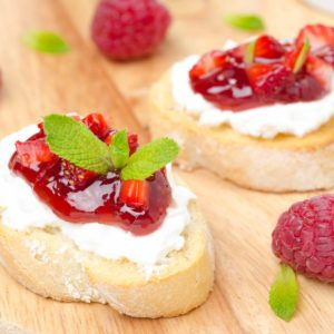 Toasted baguette with cream cheese, raspberry jam, raspberry and mint on a wooden board close-up