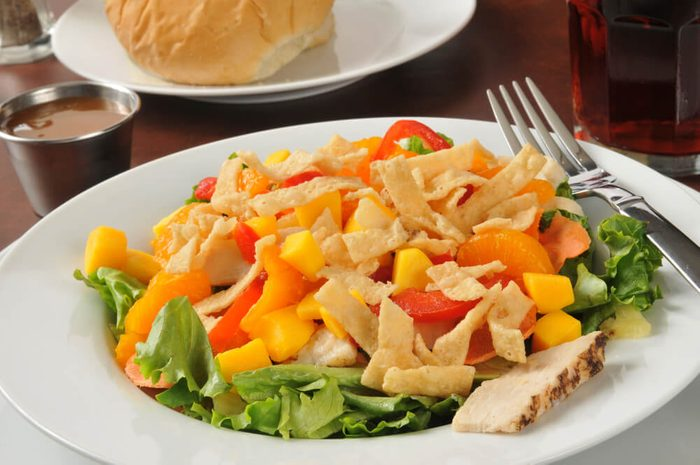 Closeup of a bowl of salad with chicken and tropical fruits