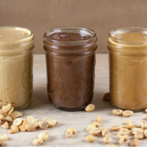 Peanut butter, hazlenut spread, and cashew butter on a wooden table
