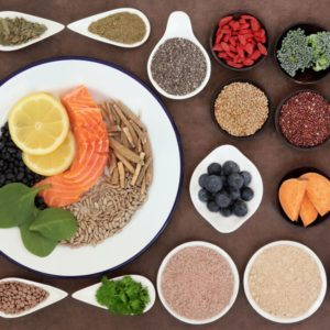 Large health food selection in bowls over lokta paper background