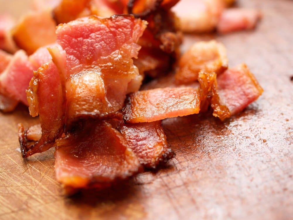 Cooked bacon pieces on wood