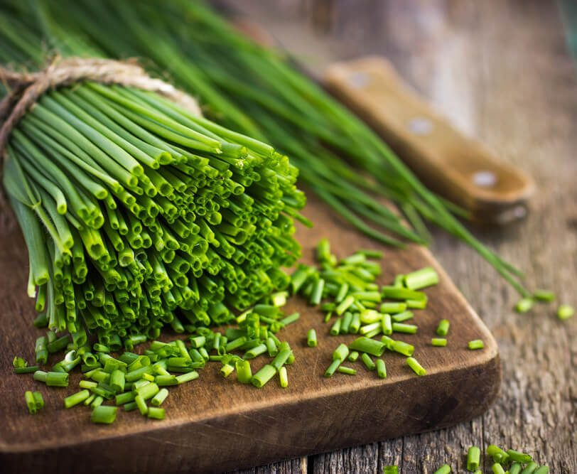 bunch of fresh chives on a wooden cutting board, selective focus