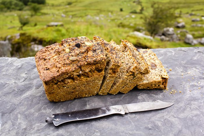 Sliced loaf of the fresh traditional Irish soda bread outside with knife aside and visible greenery on the background.
