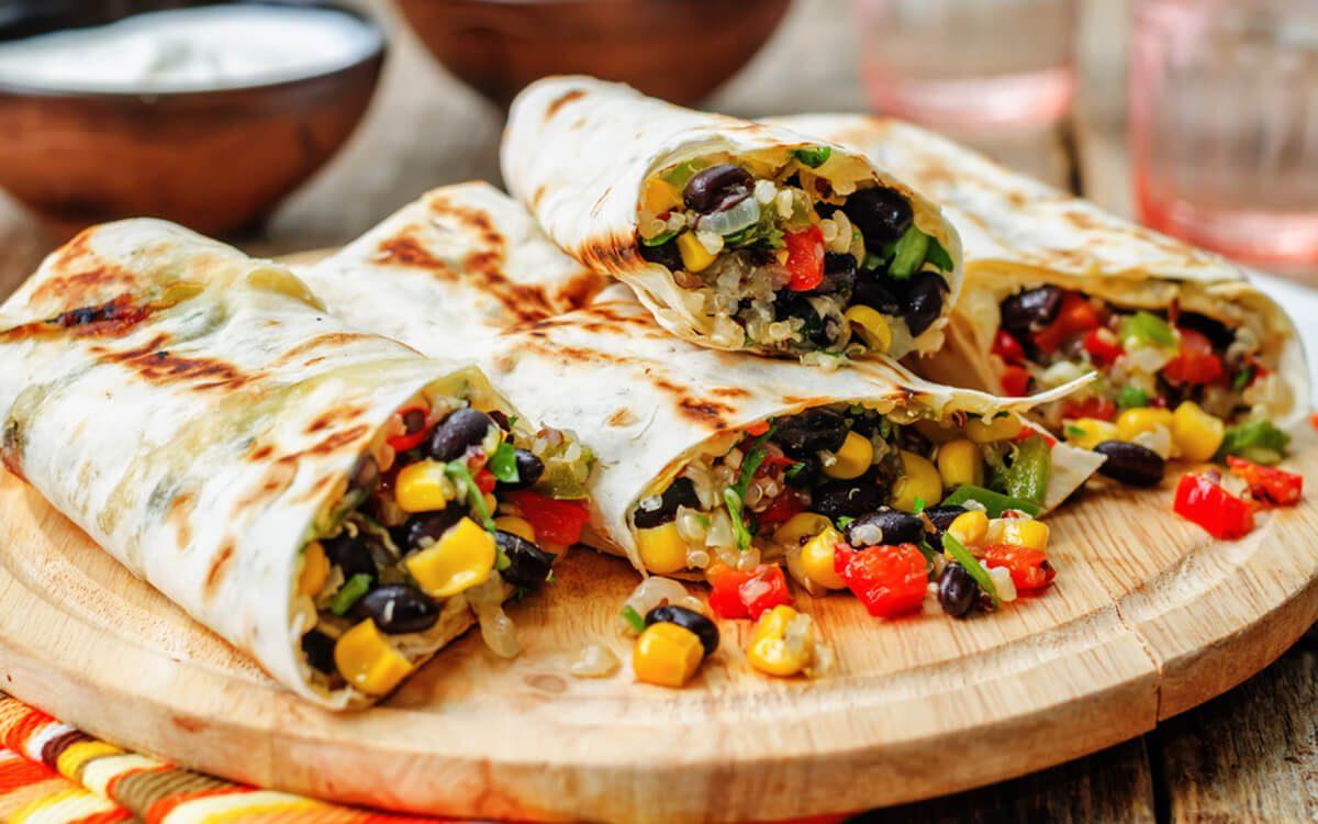 pepper corn black bean quinoa burritos on a dark wood background. the toning. selective focus
