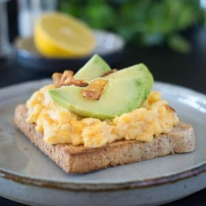 English breakfast with scrambled eggs, avocado slices and roasted bacon. Selective focus