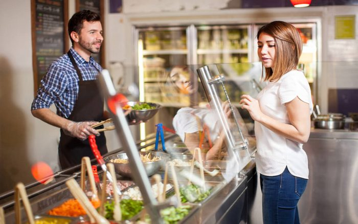 Profile view of a beautiful brunette choosing the ingredients for her salad at a restaurant