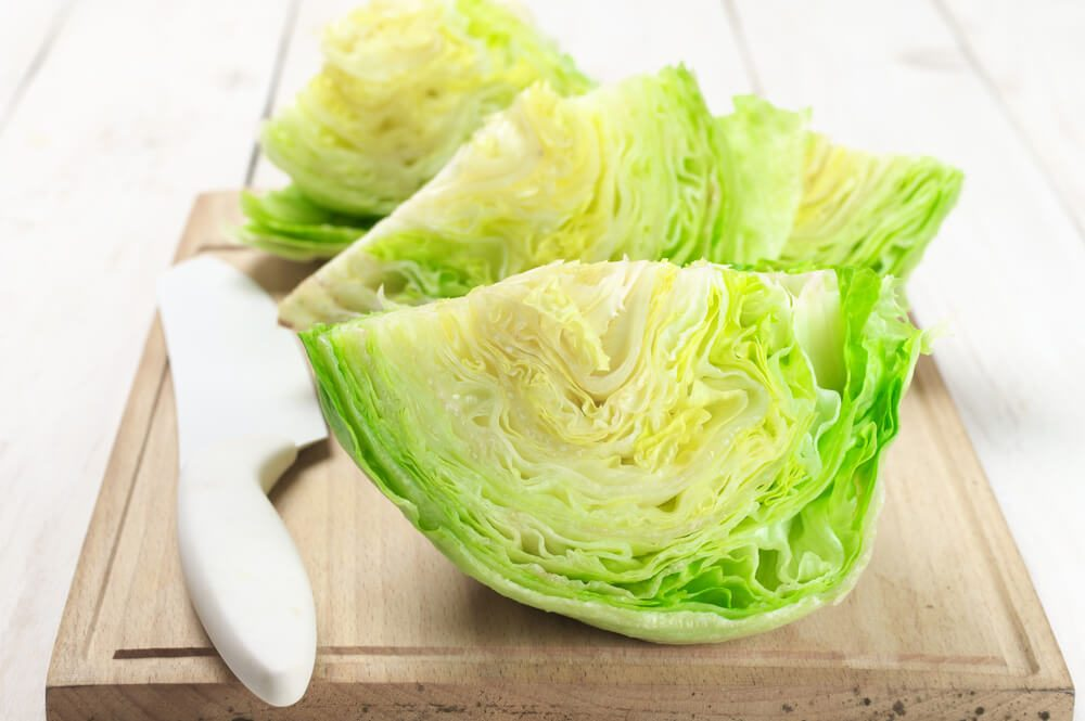 Cut pieces of iceberg lettuce with kitchen knife on cutting board