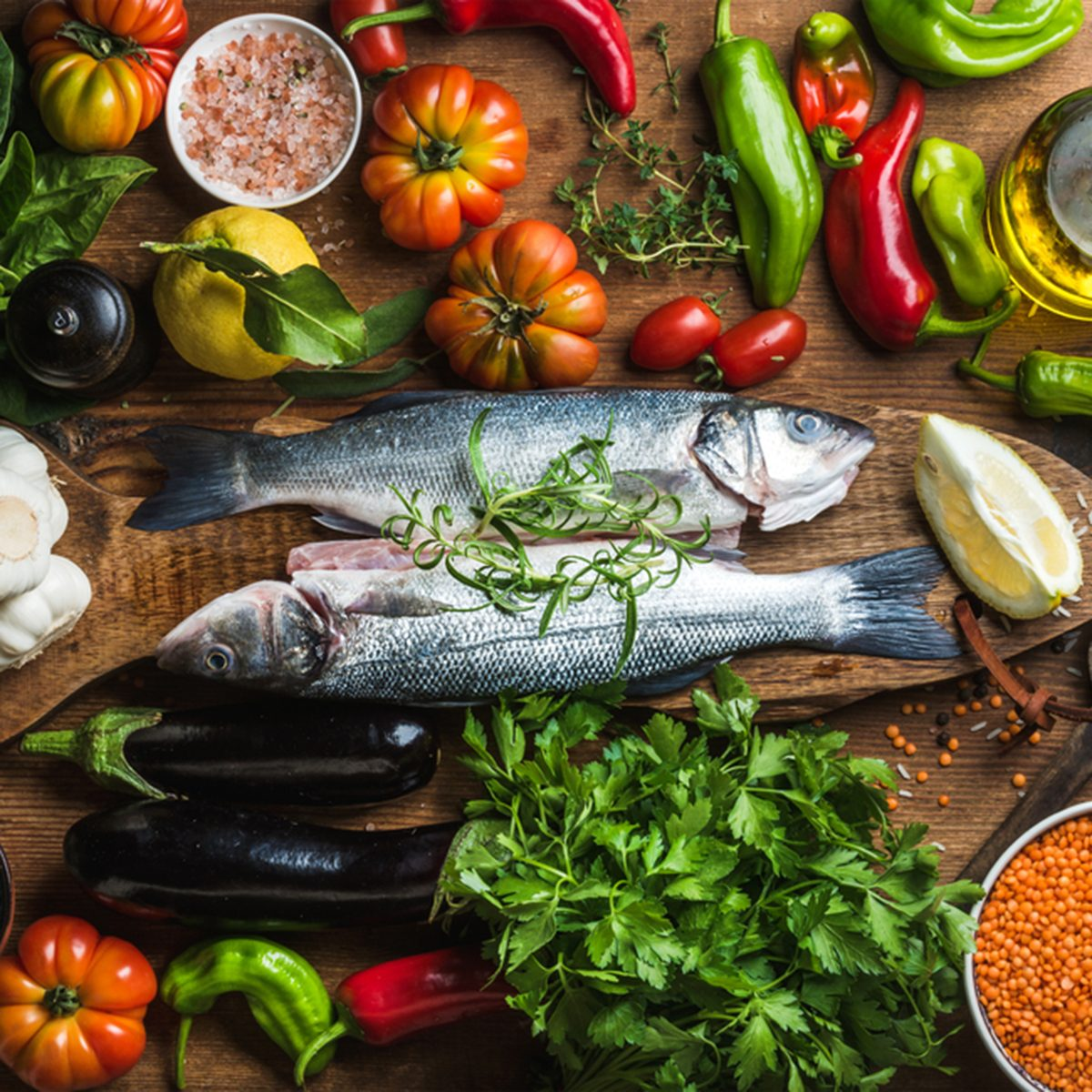 Raw uncooked seabass fish with vegetables, grains, herbs and spices on chopping board over rustic wooden background, top view; Shutterstock ID 415721434