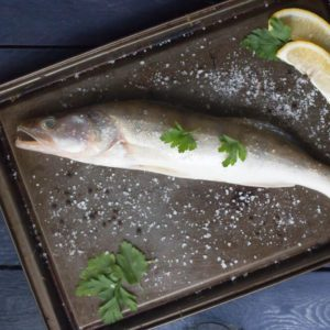 Fresh raw perch fish with spices,lemon and parsley on black background, top view