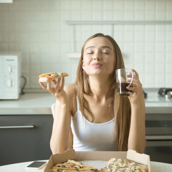 Portrait of a smiling woman holding a slice of pizza in her hand, her eyes closed with pleasure, sitting at the kitchen table, enjoying the taste of pizza.
