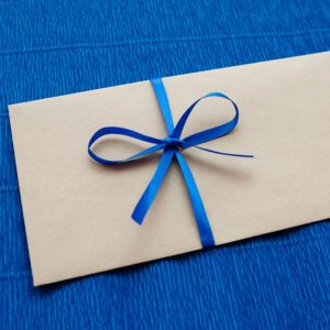 Gift kraft envelope with a blue ribbon on a blue background