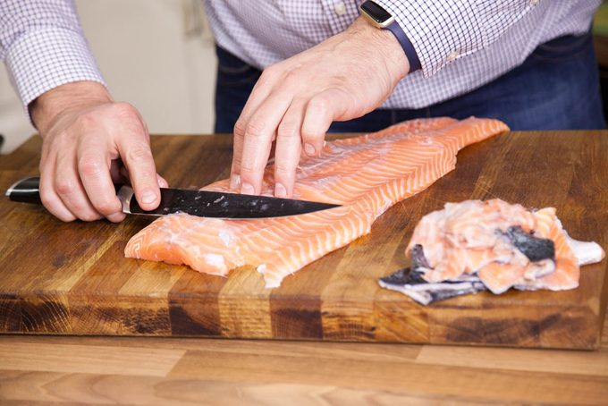 Preparing fish filet in kitchen