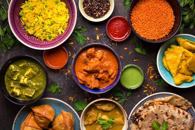 Assorted indian food on dark wooden background.