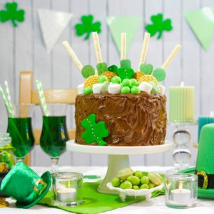 Happy St Patricks Day, March 17, green and white party table with showstopper chocolate cake decorated with candy, cookies and shamrock flags