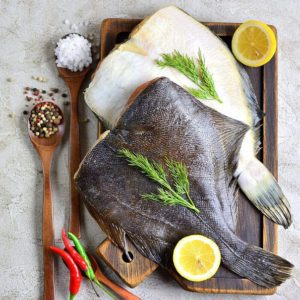 Raw fish flatfish on a wooden board with lemon and spices gray background. copy Space