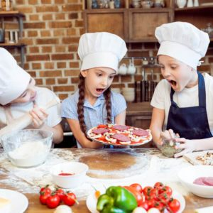 Kids cooking pizza in chefs hats