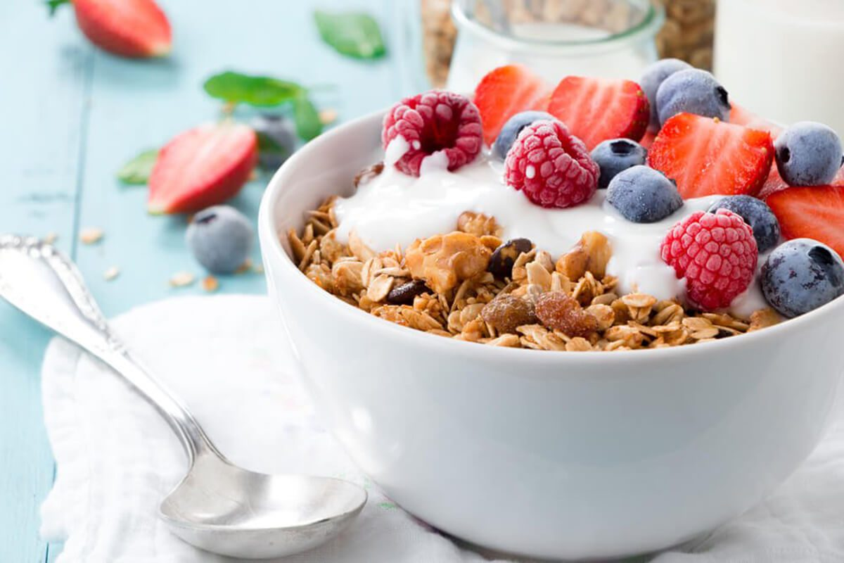 Granola in a bowl topped with yogurt and different berries