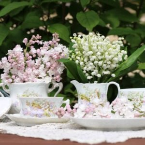 Lilac, bunch, bouquet of lily of the valley in vintage, antique authentic china, porcelain milk jug, sugar bowl, tea cup with saucer on lace napkin on table, bush background, garden floral scene
