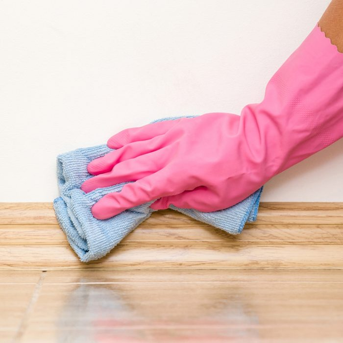 Hand in rubber protective glove cleaning baseboard on the floor from dust with microfiber rag at the wall. Early spring cleaning or regular clean up. Maid cleans house.; Shutterstock ID 664596868