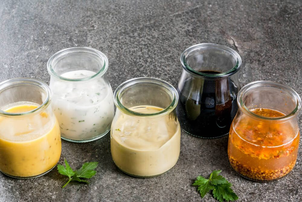 Set of organic healthy dietary dressings for salad: sauce vinaigrette, mustard, mayonnaise with spices or ranch, balsamic or soy, basil with yogurt. On a dark stone table. copy space