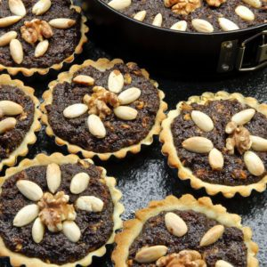 Delicious poppy tart with almonds and walnuts on marble