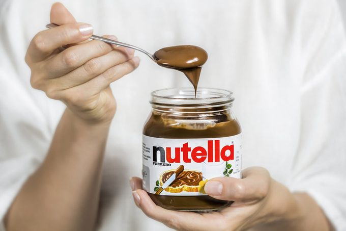 Jar of Nutella. Spoon in chocolate cream, dessert.