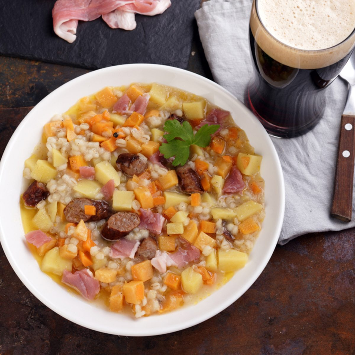 Traditional Irish dish Dublin coddle with sausages and beer on a table; Shutterstock ID 767524477