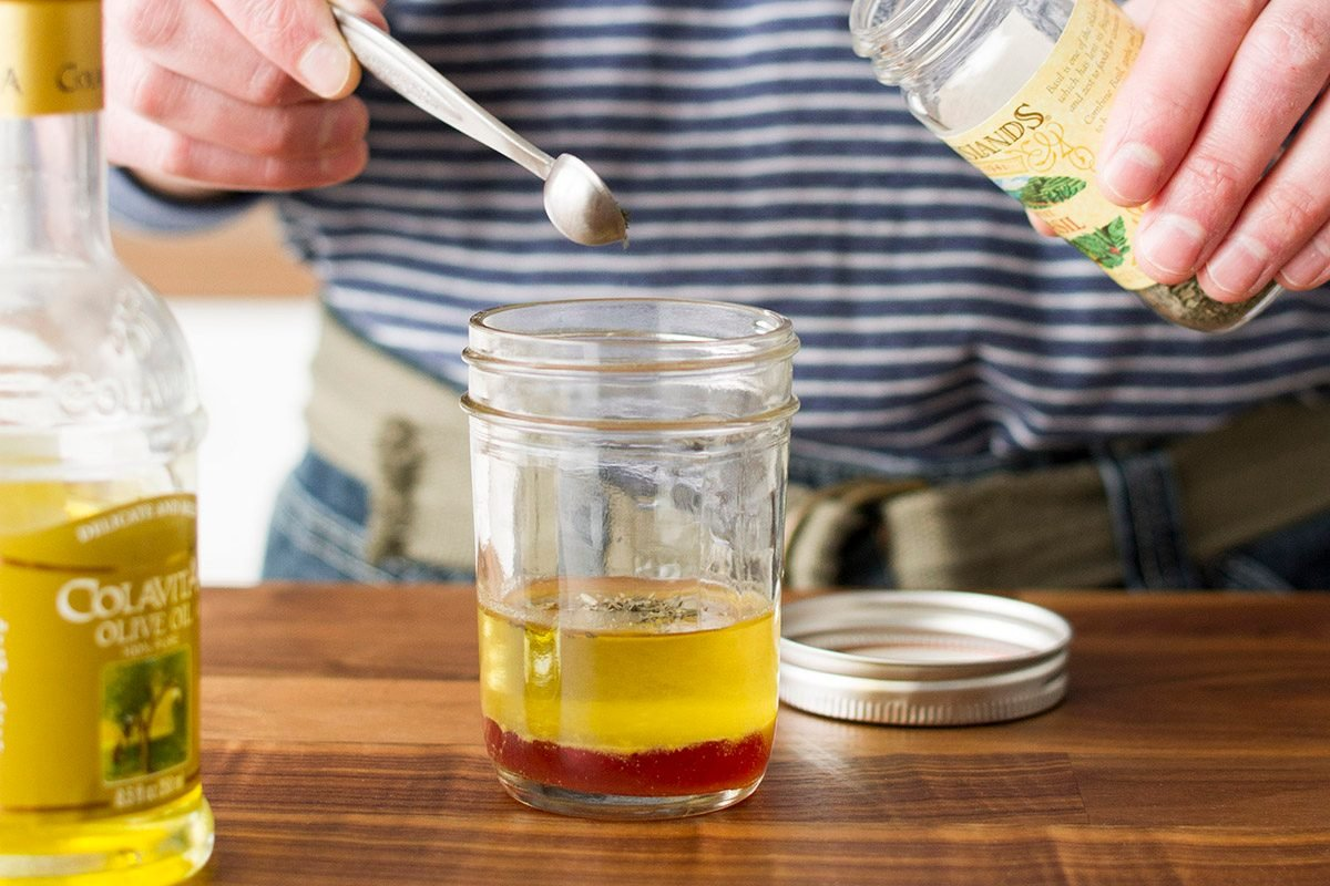 Cook making homemade vinaigrette with oil and seasoning.